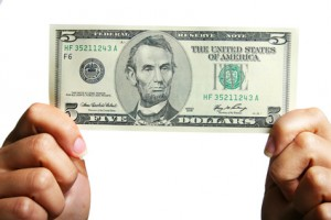 Hands holding five dollars